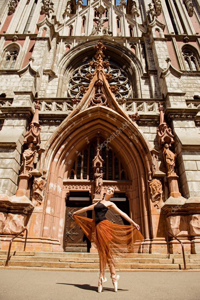 Elegant ballerina dancing in front of the ancient building
