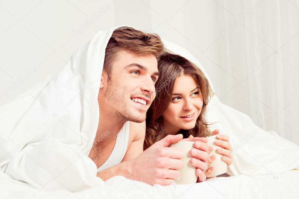 Süße junge Paare mit Tassen und lächelnd unter Decke — Stockfoto ...