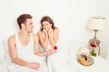 Young handsome man making a proposal in bed