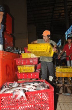 Ho Chi Minh City, Vietnam - November 28, 2013: Porters are working hard to load plenty baskets of fisheries at the Binh Dien wholesale night seafood market, the biggest one in Vietnam