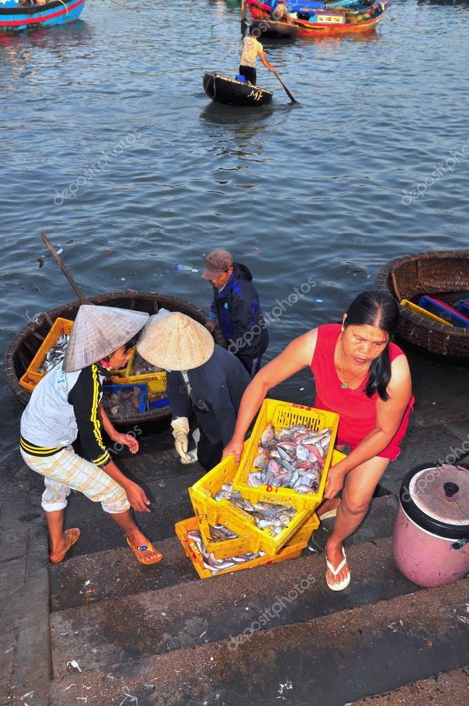 Nha Trang, Vietnam - October 5, 2011: A Woman is bringing fresh fishes upstair to a local seafood market in Vinh Luong port