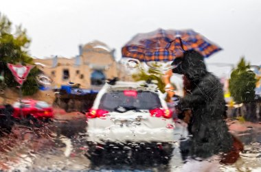 Woman with umbrella crossing streen in rain storm