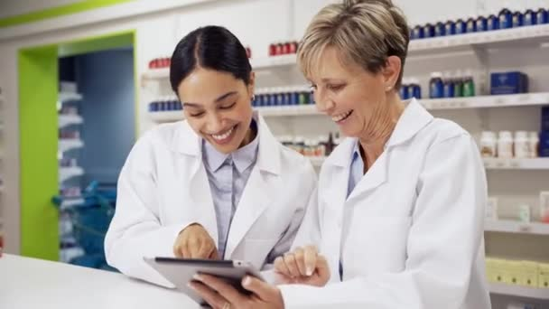Two female colleagues scrolling through emails on digital tablet standing behind prescription counter in pharmacy