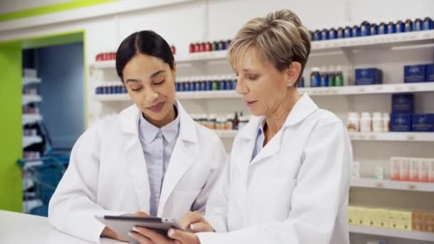 Female manager assisting intern with using digital tablet to read scripts in pharmacy