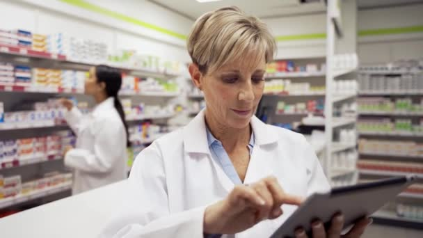 female caucasian pharmacist typing on digital tablet emailing scripts to customers wearing white coat standing in pharmacy