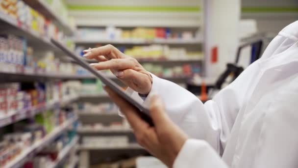 Close up of female pharmacist scrolling on digital tablet checking and counting stock of medicines on shelves in pharmacy