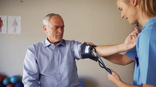 female doctor taking blood pressure of elderly man.