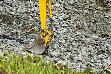 Excavator shovel digging rock on constriction site