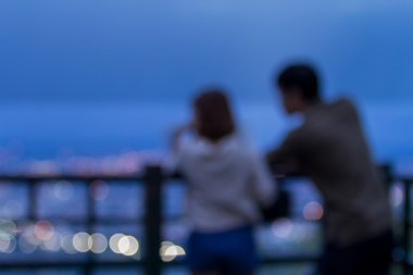 Defocused young couple and city light from viewpoint