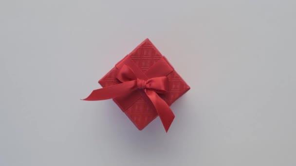 Krásná červená dárková krabice s červeným lukem rotující izolované na bílém pozadí