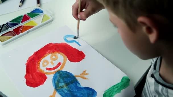 Junge zeichnet Farben auf weißem Papier