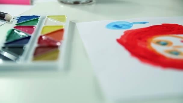 Chlapec kreslí barvy na bílém papíře