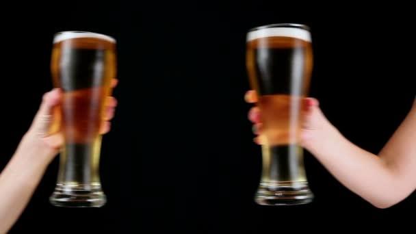 Cinkání sklenic piva na černém pozadí