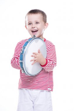 Happy boy in colorful shirt with tambourine