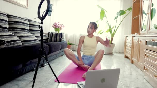 Yoga-, Pilates- und Wellness-Trainer-Training während der Sperrung in ihrer Wohnung, Live-Videoübertragung. Hispanische junge Frau unterrichtet online mit Smartphone und Laptop-Notebook.