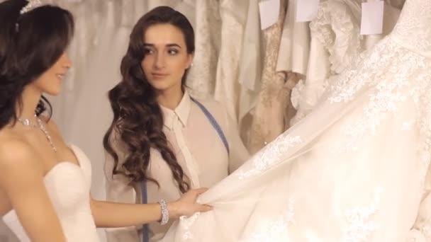Konzultant pomáhá dívka vybrat svatební šaty