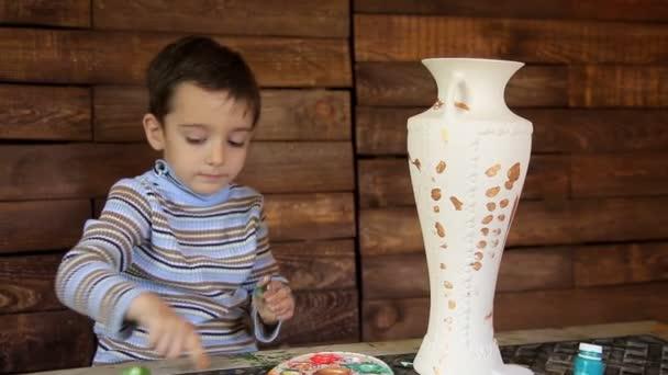 Positive child paints a ceramic vase