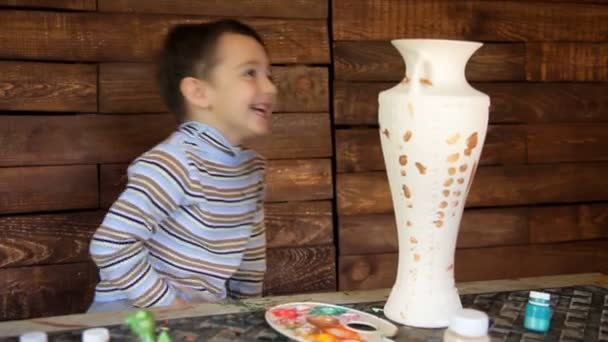 Child paints the pottery and laughs
