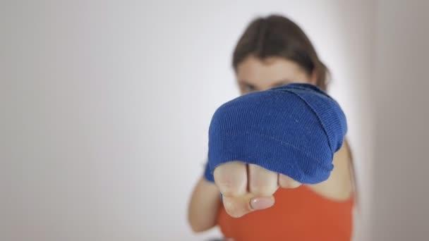 Sport realizuje koncept zdravého životního stylu. Box se sportovními kapelami. Žena se sportovními obvazy na pažích cvičí v boxu. Mladá sportovkyně pohyb cvičení