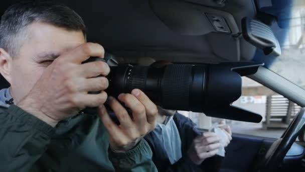 Paparazzi oder Detektive fotografieren heimlich etwas, während sie im Auto sitzen. Das Sammeln kompromittierender Beweise oder Materialien für einen Artikel
