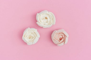 Flowers from marshmallow, sweet food background with copy space. Greeting card pastel colored. Top view and flat lay.