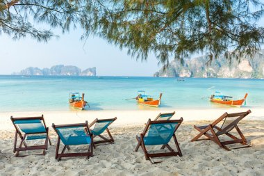 Bamboo beach chairs and traditional long-tail boats
