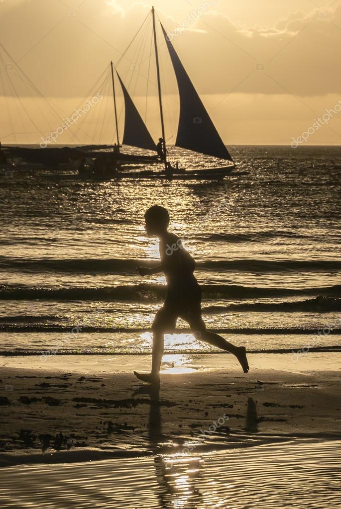 Silhouette of a running boy at amazing orange sunset with boats