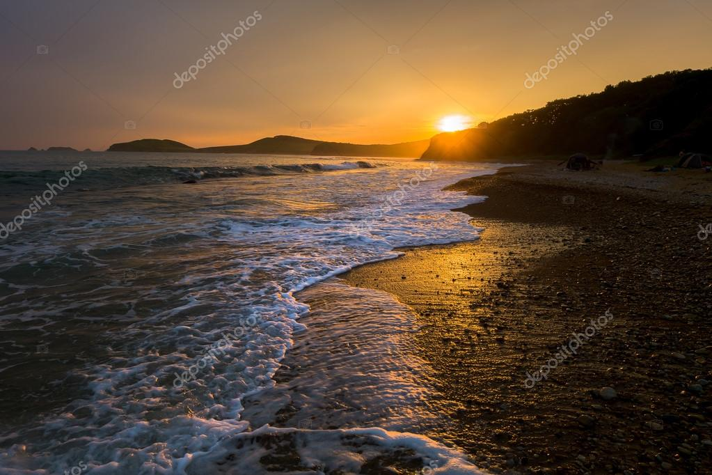 waves on the beach against sunset
