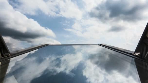 Časová prodleva mraků odrážející se ve střešním okenním skle, naklánějícím se proti obloze, rodinnému domu, domovu, mraky jsou zlověstné a přichází bouřka, pojetí pojištění a domácí bezpečnosti