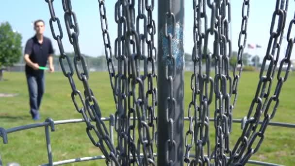 Der Blick hinter den Korb eines professionellen Discgolfers feiert nach einem entfernten Putt mit einer grünen Scheibe an einem klaren Sommertag