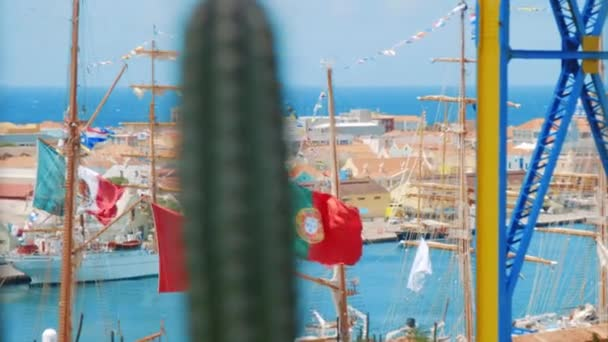 Ships docked at port with flags from Mexico Peru and Portugal flying in the breeze on a clear day with cactus defocused in the foreground