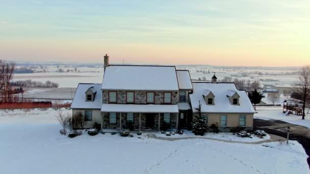 Rodinný dům v zimním západu slunce, panoramatická venkovská krajina Pensylvánie v pozadí. Kamenná fasáda s červenými okny a střechou pokrytou sněhem. Architektura, realitní anténa pořízena