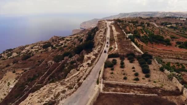 Adventurous Tourists Riding ATV's Along Coastal Road, Stunning Gozo Landscape.