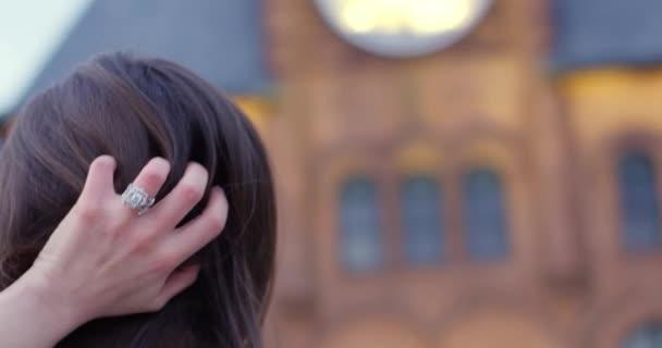 Mittlere Aufnahme eines schönen Mädchens, das vor einem Uhrenturm bei Sonnenuntergang Hand durch ihr brünettes Haar läuft