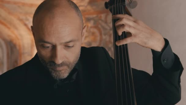 A male cellist plays his cello intently with a string quartet