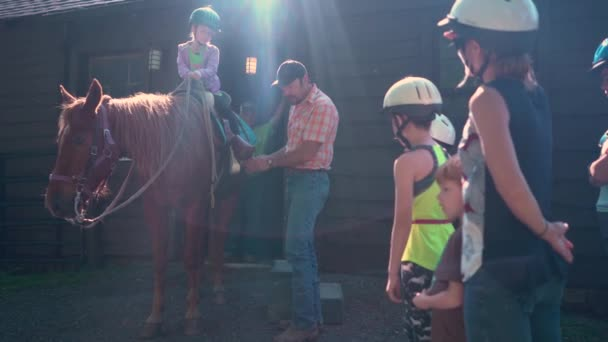 Horse handler gives instruction on how to handle a horse to a group of kids.
