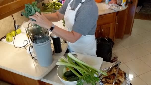 Mature woman juicing raw fruits and vegetables for health and fitness