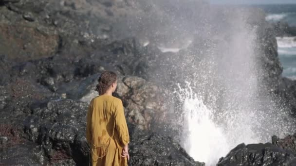 Woman Standing Next To Erupting Blow Hole On Rocky Shore