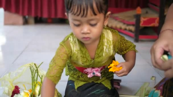 Kleines Mädchen bricht Blumen auseinander, um Blütenblätter zu Dekorationen hinzuzufügen, die zu hinduistischen Opfergaben im Tempel werden. Balinesisches Kind lernt, Opfergaben und Kunsthandwerk zu verkaufen und für religiöse Veranstaltungen zu verwenden.