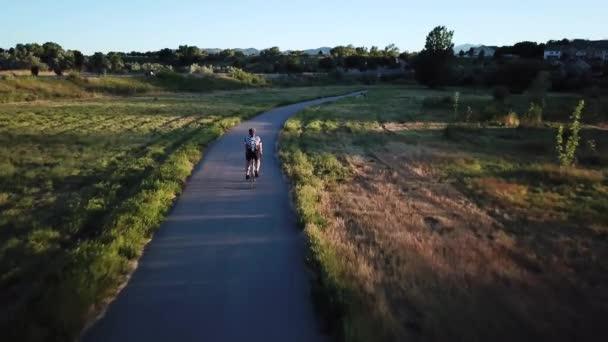 Drone Shot following a cyclist who is training for a triathlon by riding his bike down a narrow bike path.