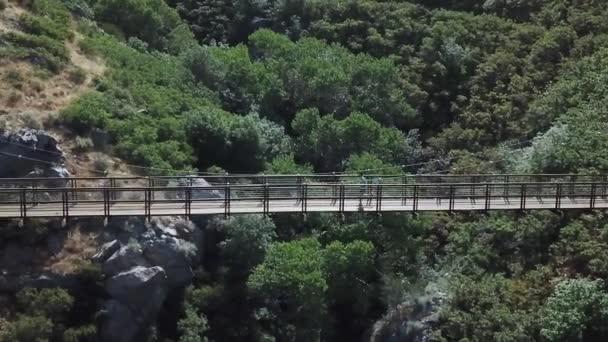 Drone Shot following an active man running on an outdoor hanging suspension bridge above Bear Canyon in Draper City, Utah.