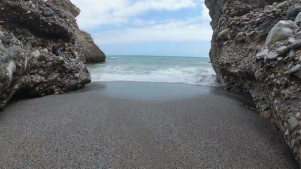 Spain Malaga Nerja beach on a summer cloudy day using a drone and a stabilised action cam. shoots of water waves people and sky at 4k 24fps