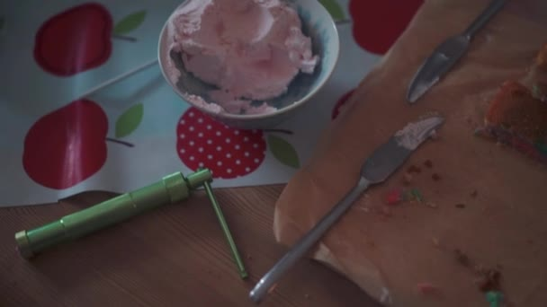 Ruční záběr někoho, kdo přidává nějaké doteky na zmrzlinový dort ve tvaru kužele.