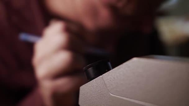 Closeup of old man inspecting diamond with a specialized microscope