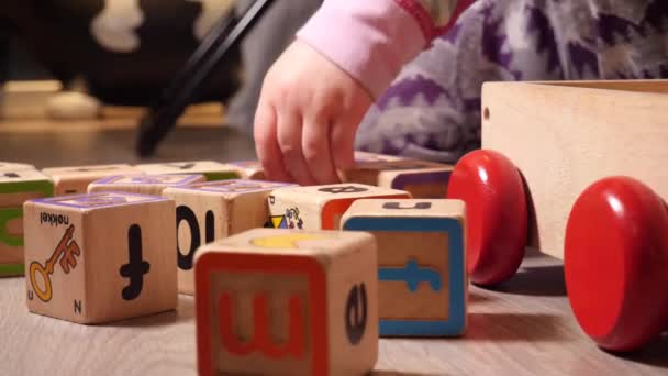 Child playing with learning building blocks with numbers and letters on them in an educational game
