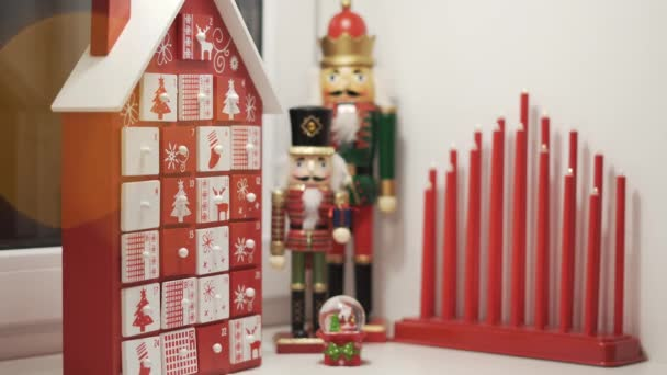 Happy Little Boy Takes Sweet From Advent Calendar House Form With Christmas Nutcrackers in Background. Traditional Christmas Calendar for Kids