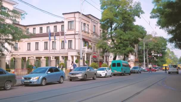A still shot of a street view of Odessa with people walking on the street and car parked beside the road.