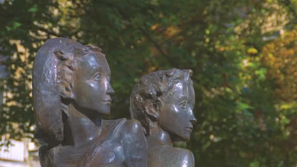 A statue of a boy and girl in the park.
