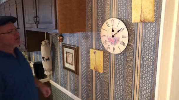 Man adjusting clock for time on kitchen wall