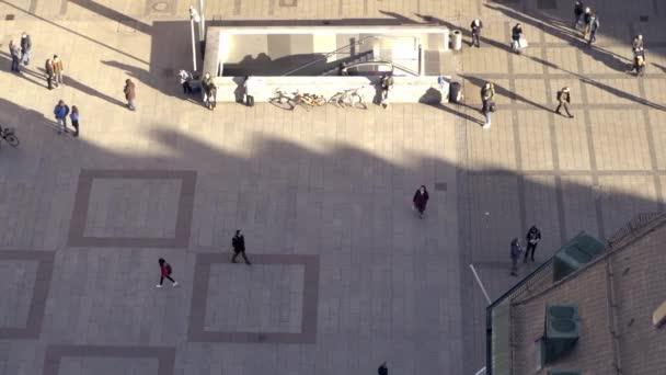Luftaufnahme vieler Menschen, die durch die Straßen einer deutschen Stadt gehen und diese erkunden. Auch Fußgänger betreten und verlassen die U-Bahn.